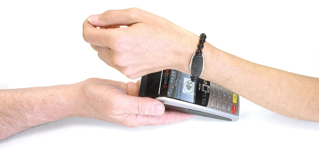 A woman paying with a K-pay Paris contactless payment bracelet whilst a man holds the payment terminal